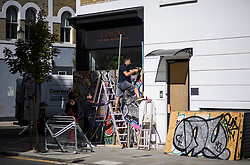 © Licensed to London News Pictures. 24/08/2018. London, UK. Workmen put up boarding to protect the windows of shops around Notting Hill, West London ahead of the 2018 Notting Hill Carnival which starts this weekend. Photo credit: Ben Cawthra/LNP