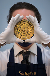 """© Licensed to London News Pictures. 29/03/2021. LONDON, UK. A staff member presents """"a unique 14th-century Astrolabe, the only known version created by a Muslim artist in a Christian-ruled city"""" (est. <br /> £600,000-800,000). Preview of the upcoming Arts of the Islamic World & India sale where historic objects, paintings and manuscripts from the last 1,000 years are to be auctioned on 31 March at Sotheby's New Bond Street galleries.  Photo credit: Stephen Chung/LNP"""