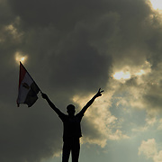 Full of hope for a better tomorrow, one man scales great heights over Cairo's Tahrir Square to raise his flag against a dramatic backdrop.