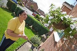 Older woman admiring a hanging basket full of flowers,