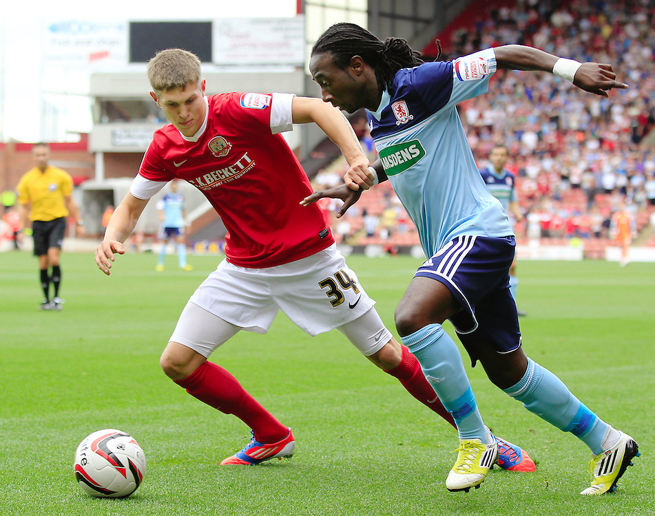 Barnsley's John Stones and Middlesbrough's Marvin Emnes challenge for the ball..Football - npower Football League Championship - Barnsley v Middlesbrough - Saturday 18th August 2012 - Oakwell Stadium - Barnsley..