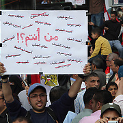 """""""Who are you?!"""" asks this man's placard, incredulously, surrounded by the crossed-out names of Mubarak, his family and other high-ranking regime officials."""