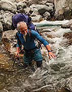 Tramper Andy Dennis crosses Canyon Creek, Canterbury, New Zealand.