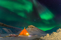A social gathering in a tent on the outskirts of Longyearbyen during the polar night. The warmth of inside the tent competes with the light show outside.