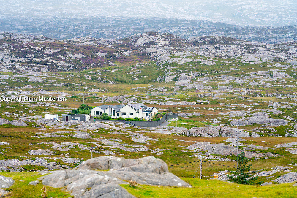 View of on solitary house amongst rocky barren landscape on The Bays on East coast of Isle of Harris, Outer Hebrides, Scotland, UK