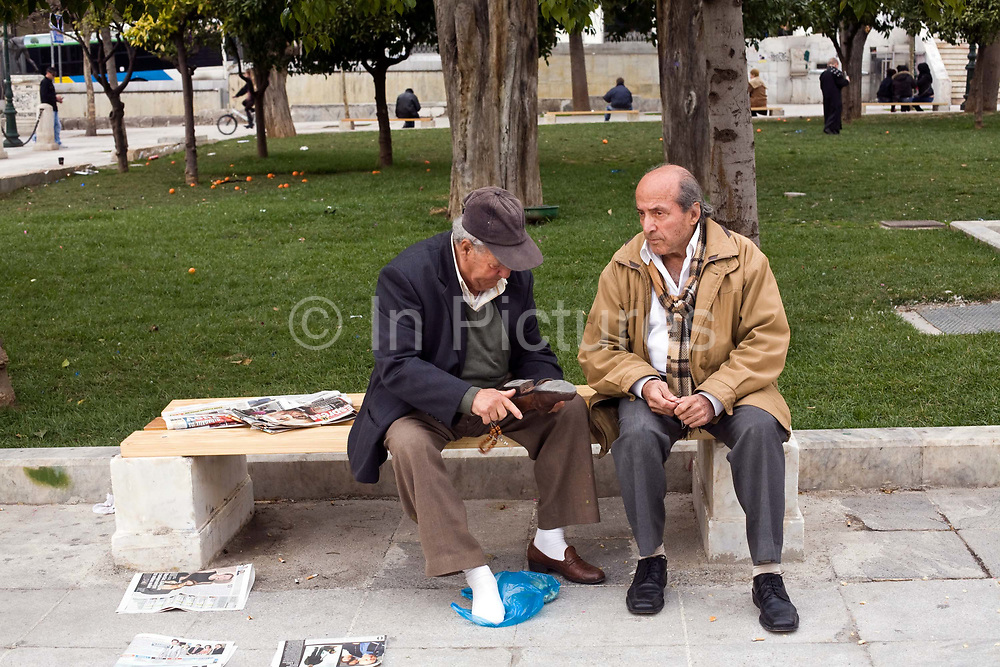 An old man shows another the sole of his shoe as they sit on a bench in Syntagma Square, Athens, Greece