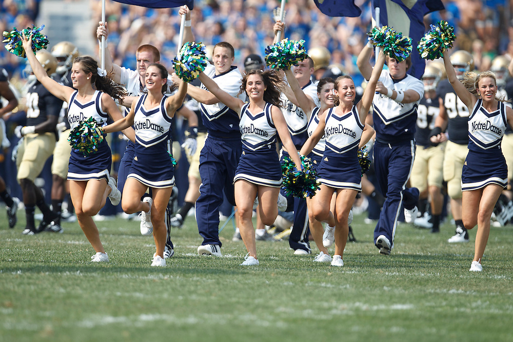 The Notre Dame cheerleaders lead the team onto to the field during NCAA football game between Notre Dame and South Florida.  The South Florida Bulls defeated the Notre Dame Fighting Irish 23-20 in game at Notre Dame Stadium in South Bend, Indiana.