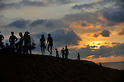 People climbing sand hills, silhouetted against rising sun. Red Sand Dunes, Mui Ne, Vietnam
