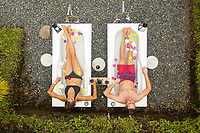 Filandia, Colombia - 08 March 2020: Aerial view of a couple relaxing in a bathtub outdoor in a resort campsite, Quindío, Colombia.