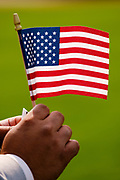 17 SEPTEMBER 2020 - DES MOINES, IOWA: A new citizen holds an American flag during a naturalization ceremony at Principal Park, a minor league baseball stadium in downtown Des Moines. About 75 people from 32 countries were naturalized as US citizens Thursday. It was the last citizenship ceremony in Des Moines before citizenship fees dramatically increase. Starting Oct. 2, the fee to apply for U.S. citizenship will increase from $640 to $1,160 if filed online, or $ 1,170 in paper filing, a more than 80% increase in cost. Advocates for immigration are afraid the new fees will be too expensive for many immigrants and say it's an effort by the Trump Administration to limit the number of new citizens welcomed into the United States. Because of the COVID-19 pandemic, there has been dramatic slow down in the number of naturalization ceremonies this year.             PHOTO BY JACK KURTZ
