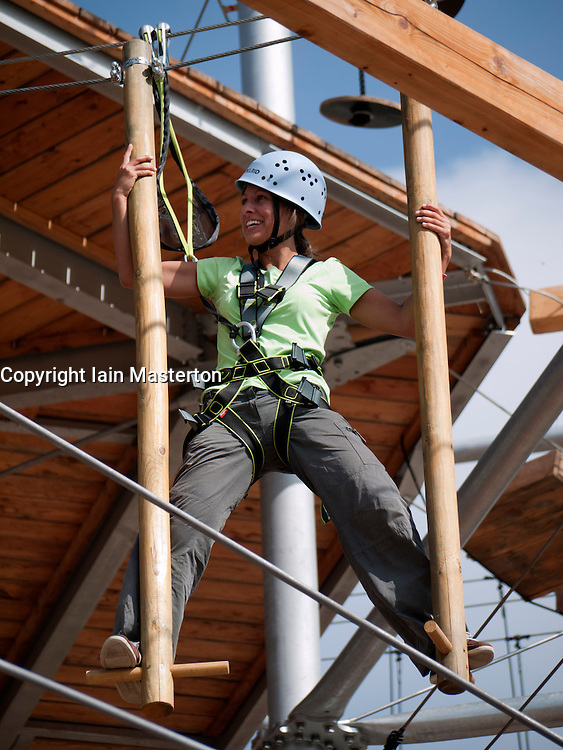 Young woman climbing on modern  new outdoor adventure playground featuring multi-level climbing and obstacle courses in Berlin Germany