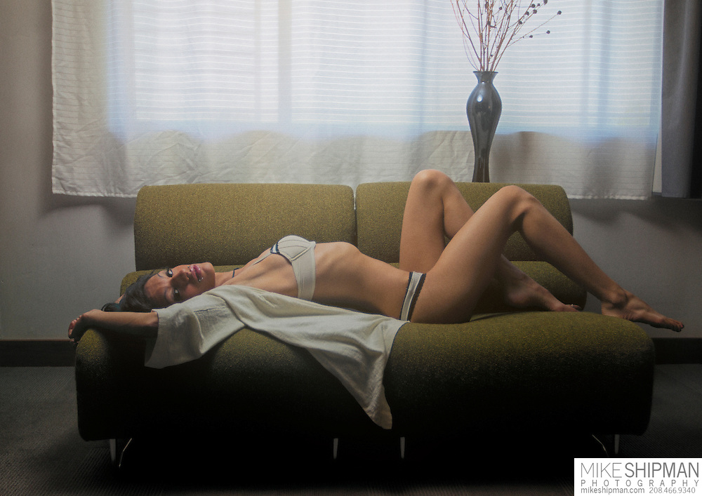 A young brunette woman wearing bra and panties reclines on a green couch.