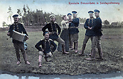 Russische grenzsoldaten in Sonntagsstimmung 1900. Russian border guards and one woman in dance poses with one border guard playing accordion.