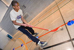 Boy playing a game of indoor hockey in the sports hall of his local leisure centre,