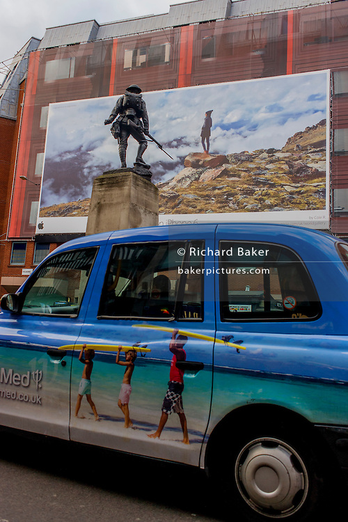 Apple iPhone billboard, juxtaposed with a WW1 foot soldier of the Royal Fusiliers and holiday taxo ad in central London.