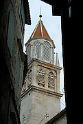 Intricately carved baroque belltower of church of Sveti Petar (Saint Peter), viewed through narrow streets. Trogir, Croatia