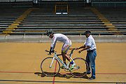 2016/06/08 - Bogotá, Colombia: Edwin Matiz, 23, gets ready to start the counter clock training, while his coach Tulio Comcel holds the bicycle on Salitre Sports Complex, Bogotá, 8th June, 2016. <br /> -<br /> Edwin has been practising Paralympic Cycling since he was 16 years old. At the age of 12, he lost his left hand while playing with an anti-personnel mine that was left on the side road by the guerrillas. The process of recuperation was long and difficult because his parents lacked financial resources. Through the help of some charities and foundations he was able to rehabilitate, mostly through the practice of cycling. After he finished high school, he started to focus 100 per cent of his time to the sport and he has managed to qualify for the Rio 2016 Paralympic Games. He dreams of a medal but he says that just to represent his country is already a good prize for now. (Eduardo Leal)