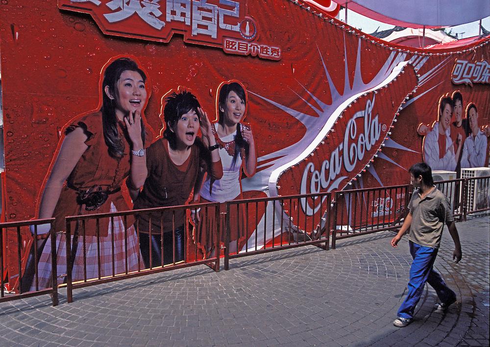 Julio 2005. Un joven observa un panel de publicidad de Coca-Cola en el centro de Shanghai.