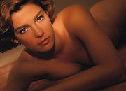 Reclining nude woman in bed  looking seductively at camera lit with warm light
