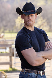 cowboy on a ranch with his arms crossed