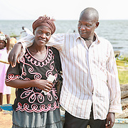 CAPTION: Peter (right) and his wife Josephine (left) came together to attend the boat race, and Josephine delighted in cheering for her husband as he took part. Here, we see them standing together after the race, in which Peter came third. LOCATION: Lake Kyoga, Abrepoli, Kaberamaido District, Uganda. INDIVIDUAL(S) PHOTOGRAPHED: Josephine Isapa (left) and Peter Ongem (right).