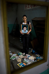 Zhao Xiao Ying, 36, holding a picture of her son Ji Qing Zhen, 12, is seen at Fuxin No.2 Primary  School in Wufu, Sichuan province.