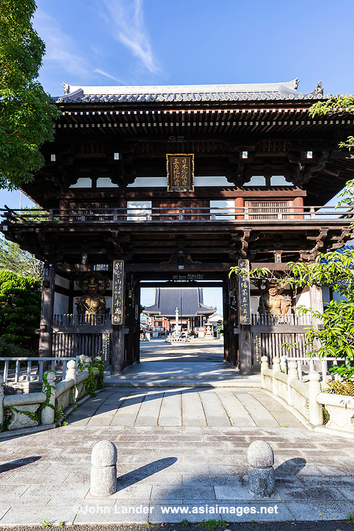 """Nankobo is temple No. 55 with a magnificent gate facing the main road, with four fierce guardians decorated with gold leaf.  The daishido is large and impressive. It's the only temple of the 88 to be called """"bo"""" instead of the typical """"ji"""". """"Bo"""" means """"small Buddhist temple"""", which is ironic because Nankobo is one of the biggest of the 88. It stands in what is in effect a religious agglomeration, a complex of sandy plazas dotted with temple and shrine buildings that stretches for three city blocks.  Although it isn't immediately obvious, themain hall of Nankobo is made of concrete. The original building was destroyed in the bombing of Imabari during WWII. The wooden gate at the entrance to the temple is of recent construction too, although its style is old. Thetemple guardians housed in the gate, front and back, are magnificently ferocious and expressive with their wooden and gilt highlights."""