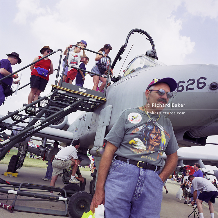 A visitor to Oshkosh Air Venture, the world?s largest air show in Wisconsin USA, stands by an A-10 Thunderbolt Tank Buster or Warthog. Wearing a t-shirt depicting a Cherokee Indian and a Bald Eagle, the tourist awaits family as aviation enthusiasts climb steps to the aircraft's cockpit. The Fairchild-Republic A-10 Thunderbolt II is a single-seat, twin-engine jet aircraft designed to provide close air support of ground forces by attacking tanks, armoured vehicles, and other ground targets. It has also been involved with British friendly fire incidents in Iraq. Close to a million populate the mass fly-in over the week, a pilgrimage worshipping all aspects of flight. Picture from the 'Plane Pictures' project, a celebration of aviation aesthetics and flying culture, 100 years after the Wright brothers first 12 seconds/120 feet powered flight at Kitty Hawk,1903.