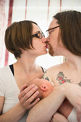 Parents holding newborn baby boy while kissing each other, Munich, Bavaria, Germany