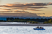 At sunset, see Mount McKinley from the confluence of the Talkeetna and Susitna Rivers at Talkeetna, Alaska, USA. Paddle in a sightseeing raft. Denali (20,310 feet or 6191 meters, aka Mount McKinley) is the highest mountain peak in North America. Measured from base to peak, it is earth's tallest mountain on land. Mount McKinley is a granitic pluton uplifted by tectonic pressure while erosion has simultaneously stripped away the somewhat softer sedimentary rock above and around it.