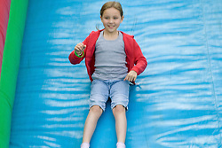 Girl enjoying the big inflatable slide at a Parklife summer activities event,