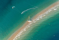 Aerial view of person kitesurfing around stranded sailboat on sandbank in the Gulf of Patras, Greece.