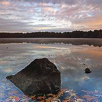 Lake Cochituate borders the Boston suburbs Natick, Wayland and Framingham and is part of the Cochituate State Park in Massachusetts. This peaceful fall foliage photography image was captured on a quiet morning at the end of autumn season - katahum. The early morning light painted the New England scenery in beautiful colors and warm hues. A mixture of blue sky and clouds and the bolder surrounded by autumn leaves provided perfect background and foreground elements for this Massachusetts nature photography image. I love experience the quietude that comes with an early morning photo outing. <br />