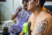 """22 MARCH 2013 - NAKHON CHAI SI, NAKHON PATHOM, THAILAND: A man gets a tattoo at Wat Bang Phra during the tattoo festival. Wat Bang Phra is the best known """"Sak Yant"""" tattoo temple in Thailand. It's located in Nakhon Pathom province, about 40 miles from Bangkok. The tattoos are given with hollow stainless steel needles and are thought to possess magical powers of protection. The tattoos, which are given by Buddhist monks, are popular with soldiers, policeman and gangsters, people who generally live in harm's way. The tattoo must be activated to remain powerful and the annual Wai Khru Ceremony (tattoo festival) at the temple draws thousands of devotees who come to the temple to activate or renew the tattoos. People go into trance like states and then assume the personality of their tattoo, so people with tiger tattoos assume the personality of a tiger, people with monkey tattoos take on the personality of a monkey and so on. In recent years the tattoo festival has become popular with tourists who make the trip to Nakorn Pathom province to see a side of """"exotic"""" Thailand. The 2013 tattoo festival was on March 23.    PHOTO BY JACK KURTZ"""