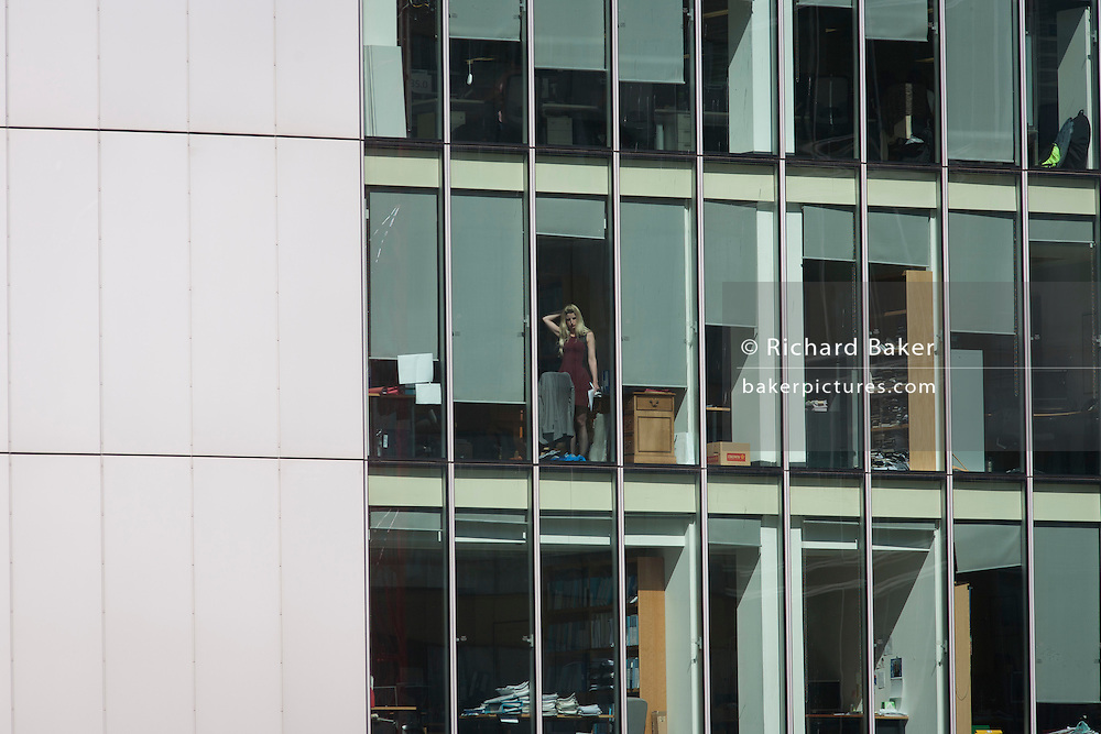 A female employee stares out the window of her office in the City of London.