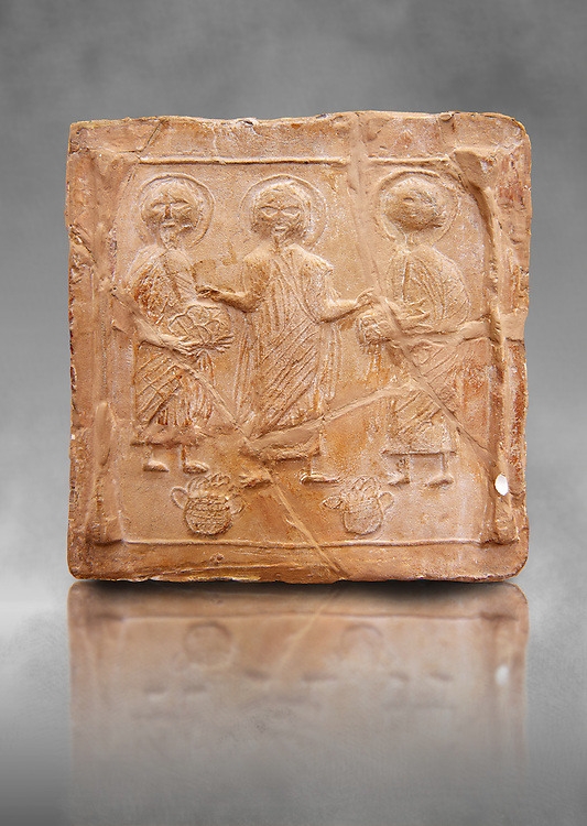 6th-7th Century Eastern Roman Byzantine  Christian Terracotta tiles depicting Christ changing Water into wine - Produced in Byzacena -  present day Tunisia. <br /> <br /> These early Christian terracotta tiles were mass produced thanks to moulds. Their quadrangular, square or rectangular shape as well as the standardised sizes in use in the different regions were determined by their architectonic function and were designed to facilitate their assembly according to various combinations to decorate large flat surfaces of walls or ceilings. <br /> <br /> Byzacena stood out for its use of biblical and hagiographic themes and a richer variety of animals, birds and roses. Some deer and lions were obviously inspired from Zeugitana prototypes attesting to the pre-existence of this province's production with respect to that of Byzacena. The rules governing this art are similar to those that applied to late Roman and Christian art with, in the case of Byzacena, an obvious popular connotation. Its distinguishing features are flatness, a predilection for symmetrical compositions, frontal and lateral representations, the absence of tridimensional atti-tudes and the naivety of some details (large eyes, pointed chins). Mass production enabled this type of decoration to be widely used at little cost and it played a role as ideograms and for teaching catechism through pictures. Painting, now often faded, enhanced motifs in relief or enriched them with additional details to break their repetitive monotony.<br /> <br /> The Bardo National Museum Tunis, Tunisia. Against a grey art background.