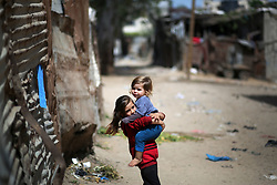 May 22, 2019 - Gaza, gaza strip, Palestine - A Palestinian girle carries his brother outside a house in an impoverished area in Beit Lahia in the northern Gaza Strip on May 22, 2019. (Credit Image: © Majdi Fathi/NurPhoto via ZUMA Press)