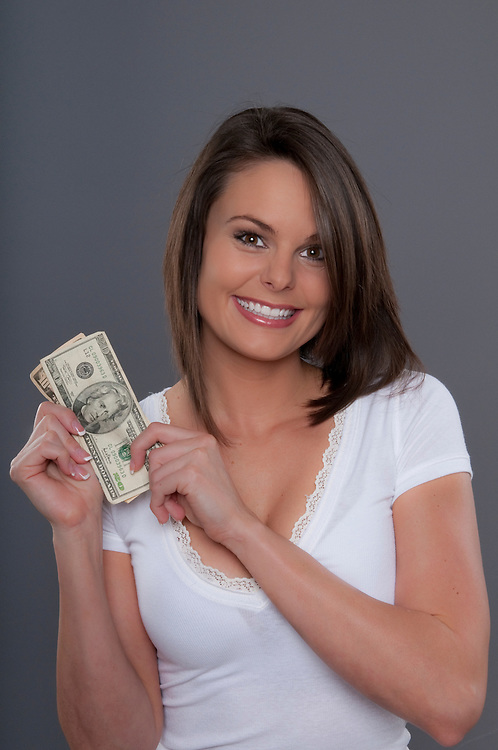 Young cucasian woman very happy with cash in hands.