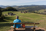 From the viewpoint of the hillside chairlift, a grass meadow landscape, a Polish visitor looks down on the Polish village of Jaworki, on 21st September 2019, in Jaworki, near Szczawnica, Malopolska, Poland.