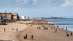 Portobello, Scotland, UK. 21 Feb 2021. After days of rain sunshine and mild temperatures brought crowds of people to Portobello beach and promenade today.  Iain Masterton/Alamy Live News