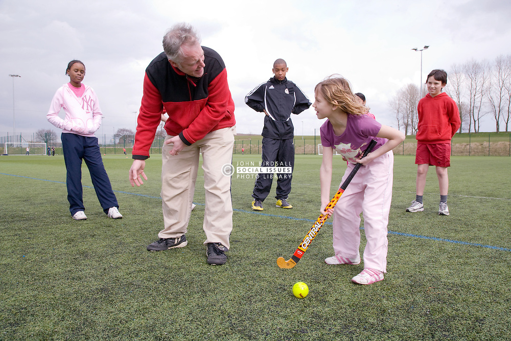 Group of children practicing hockey with their trainer on a playing field at their local leisure centre,