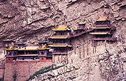 "The ""suspended in the air"" monastery, correctly known as Xuankong Si, precariously hangs off the Heng Shan mountain range, 65 Kms  south east of Datong city, west of Beijing northern Shanxi province. <br /> This current temple dates back to the 6th century, is comprised of 40 halls of differing sizes, interconnected with narrow walkways or corridors on varying levels. It contain numerous  small shrines with 80 statues of Confucian, Buddhist and Daoist gods in stone, iron, clay and bronze. It attracts vast numbers of Chinese pilgrims and tourists which travel and marvel at its astonishing feat of architectural engineering seen most impressively as you look down into the deep ravine which lies directly below the monastery, apart from its fair share of rain, storms, and earthquakes that have never destroyed this architectural wonder."