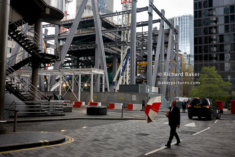 Businessmen with corporate umbrella passes beneath a new construction project in London's financial district, the Square Mile.