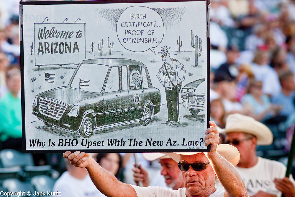 """May 29 - TEMPE, AZ: A man with an anti-Obama cartoon at a Tea Party rally in Tempe, AZ. About 3,000 people attended a """"Buy Cott Arizona"""" rally at Tempe Diablo Stadium in Tempe, AZ Saturday night. The rally was organized by members of the Arizona Tea Party movement to show support for Arizona law SB1070. The """"Buy Cott"""" is a reaction to the economic boycott planned by opponents of SB1070. SB1070 makes it an Arizona state crime to be in the US illegally and requires that immigrants carry papers with them at all times and present to law enforcement when asked to. Critics of the law say it will lead to racial profiling, harassment of Hispanics and usurps the federal role in immigration enforcement. Supporters of the law say it merely brings Arizona law into line with existing federal laws.  Photo by Jack Kurtz"""