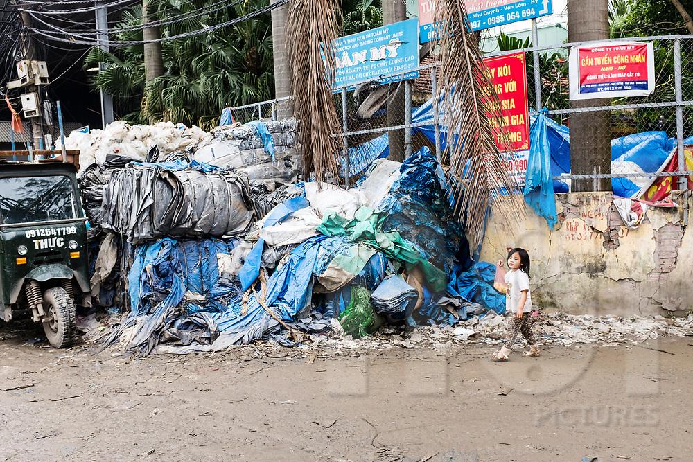 Young Vietnamese girl walks nearby big stacks of plastic, Minh Khai village, Hung Yen Province, Vietnam, Southeast Asia