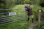 Countryside walkers pass through a gate before closing it again afterwards - a requirement of the countryside code, on 10th September 2018, near Lingen, Herefordshire, England UK.