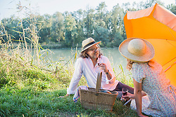 Couple having a picnic and drinking wine by lakeshore, Bavaria, Germany
