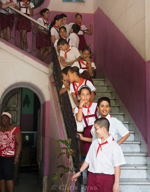 Schoolchildren in uniform waiting on stairs, Havana, Cuba