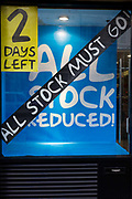 The front of an outdoor shop's end of business sale where all stock is reduced and must go within 2 days. A detail of the shop's window shows the diagonal sticker across the glass telling potential street customers that all their goods must be sold soon before the store closes in 2 day's time. These are hard economic times and high-street shops are closing as first the credit crunch followed by recession then government cuts have led to thousands of businesses have been forced to close.
