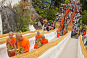 "15 JULY 2011 - PHRA PHUTTHABAT, SARABURI, THAILAND:   Monks make the final ascent to the temple up a flight of stairs during the Tak Bat Dok Mai at Wat Phra Phutthabat in Saraburi province of Thailand, Friday, July 15. Wat Phra Phutthabat in Phra Phutthabat, Saraburi, Thailand, is famous for the way it marks the beginning of Vassa, the three-month annual retreat observed by Theravada monks and nuns. The temple is highly revered in Thailand because it houses a footstep of the Buddha. On the first day of Vassa (or Buddhist Lent) people come to the temple to ""make merit"" and present the monks there with dancing lady ginger flowers, which only bloom in the weeks leading up Vassa. They also present monks with candles and wash their feet. During Vassa, monks and nuns remain inside monasteries and temple grounds, devoting their time to intensive meditation and study. Laypeople support the monastic sangha by bringing food, candles and other offerings to temples. Laypeople also often observe Vassa by giving up something, such as smoking or eating meat. For this reason, westerners sometimes call Vassa the ""Buddhist Lent."" The tradition of Vassa began during the life of the Buddha. Most of the time, the first Buddhist monks who followed the Buddha did not stay in one place, but walked from village to village to teach. They begged for their food and often slept outdoors, sheltered only by trees. But during India's summer rainy season living as homeless ascetics became difficult. So, groups of monks would find a place to stay together until the rain stopped, forming a temporary community. Wealthy laypeople sometimes sheltered monks on their estates. Eventually a few of these patrons built permanent houses for monks, which amounted to an early form of monastery.     PHOTO BY JACK KURTZ"